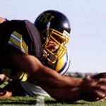 American footballer diving to catch ball whilst being tackled
